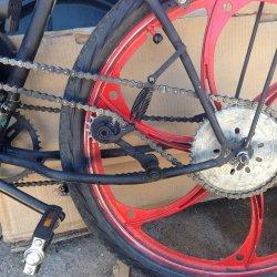 Idler sprocket spring loaded chain tensioner